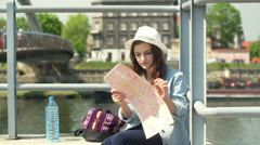 Girl sitting on the bridge next to the water and reading map Stock Footage