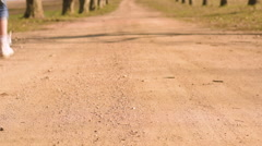 Three girls sisters running skipping down dirt road tree lined avenue Stock Footage
