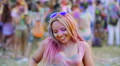 Beautiful young lady moving sexy body to music at color festival, vertical pan 4k or 4k+ Resolution