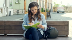 Pretty girl listening music and writing something in notebook on the bench Stock Footage