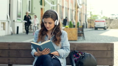 Pretty girl listening music on headphones while reading book on the bench Stock Footage
