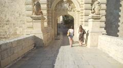 Old city entrance main door bridge cobblestones pan up wall- Stock Footage