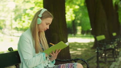 Pretty girl listening music on headphones and writing something in her notebook Stock Footage