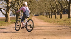 Young girl riding her bicycle bike down dirt road tree lined avenue Stock Footage