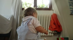Back of baby toddler playing with plastic container in baby room Stock Footage