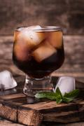 Cold drink with ice on wooden vintage table Stock Photos