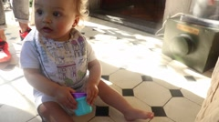 Baby boy getting up from floor and holds to chair. Baby toddler learning to walk Stock Footage