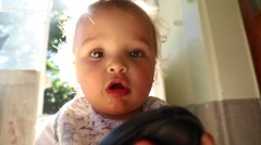 Baby trying to put camera lens cap. Revealing baby dark to light.  Stock Footage