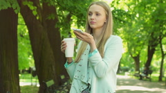 Pretty girl talking on loudspeaker while standing on path in the park Stock Footage