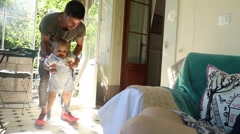 Baby toddler learning to walk with the help of parents. Stock Footage