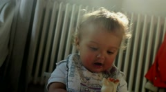 Cute baby smiling to camera. Lens flare hitting camera giving it a glow effect. Stock Footage