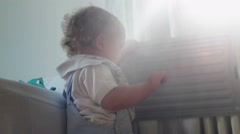 Baby playing plastic container. Lens flare hitting camera Stock Footage