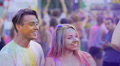 Cheerful couple moving to music in crowd at party, colored powder sprayed in air 4k or 4k+ Resolution