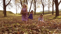 Young girls children kids playing running in fallen autumn leaves Arkistovideo