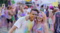 Happy friends hanging out at color festival, romantic couple hugging and dancing Footage