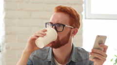 Man with Beard and Red Hairs Using Smartphone, Phone and Drinking Coffee, Tea Stock Footage