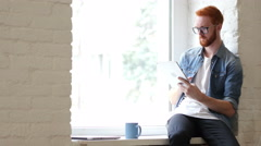 Man with Beard and Red Hairs Using Tablet for Work and Browsing Information Stock Footage