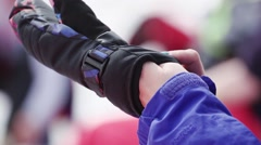 Girl in ski uniform put on black glove on ski resort. Sport event. Encamp Stock Footage