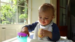 Close up of adorable cute baby toddler blonde boy on high chair. Portrait of bab Stock Footage