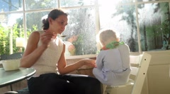 Mother and baby together at home balcony during golden hour lens flare sunset Stock Footage
