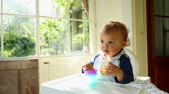 Close up of adorable cute baby toddler blonde boy on high chair. Stock Footage