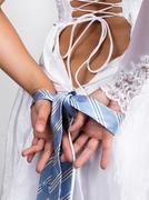 Bride putting on her white wedding dress, closeup bride's hands are linked male Stock Photos