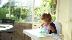 Baby playing with toys while sitting on high chair Stock Footage