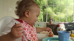 Baby playing with food leftovers Stock Footage