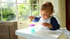 Happy baby boy playing with toys while sitting on high chair. Adorable cute baby Stock Footage