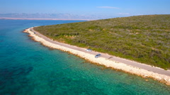 White car driving next to sea beach aerial view 4K Stock Footage