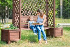 Mother with son sitting on a bench in park and reading book Kuvituskuvat