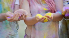 Excited young people throwing coloured powder in air, shining with happiness Stock Footage
