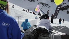 Little girl in cap made of foil lie with yellow air balloon. Snowboarder riding Stock Footage