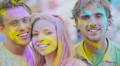 Excited faces of beautiful young people covered in colors smiling at camera 4k or 4k+ Resolution