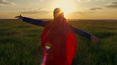 Boy dressed with a Superman cape running in a field, looking into the sunset Arkistovideo