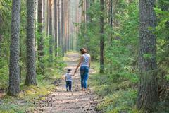 Mother and baby walk on country rural road in pine forest Stock Photos