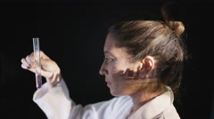 4K Scientist looking at test tube with scenes of war projected onto her face Stock Footage