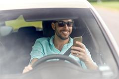 Happy man in shades driving car with smartphone Kuvituskuvat