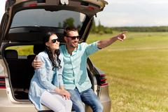 Happy couple hugging at open hatchback car trunk Stock Photos
