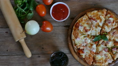 4K Dolly through ingredients to fresh made pizza, Top view on wood table Stock Footage