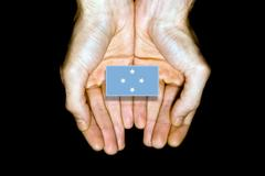 Flag of Micronesia in hands on black background Stock Photos