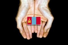 Flag of Mongolia in hands on black background Stock Photos