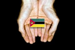 Flag of Mozambique in hands on black background Stock Photos
