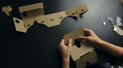 Girl assembling a Virtual Reality cardboard glasses Stock Footage