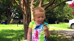 Little red haired girl with a Painted Lady Butterfly on her finger. Stock Footage