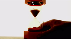 Man's hand places a bright orange backlit sand timer. Stock Footage