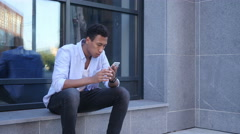 Outdoor Browsing on Smartphone, Sitting Young Black Handsome Man Stock Footage
