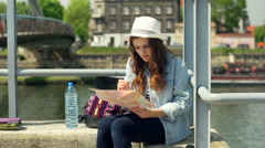 Girl sitting on the bridge and mark something on map while checking smartphone Stock Footage
