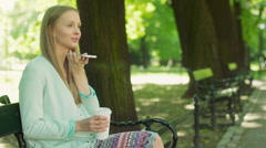 Happy girl drinking coffee on the bench and talking on loudspeaker Stock Footage
