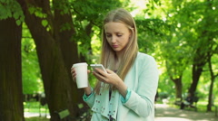 Irritated girl texting sms on smartphone while waiting for someone in the park Stock Footage